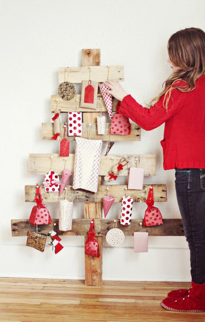 sapin en bois faits avec des planches croisées, ornements et cadeaux enrobés de papier décoratif rouge et blanc, cadeaux blancs à pois rouges