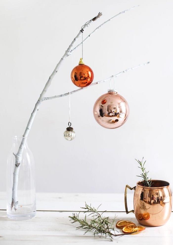 branche blanche dans une bouteille en plastique décorée de boules de noel taille variée, tasse en cuivre, romarin, tranches d orange séchées