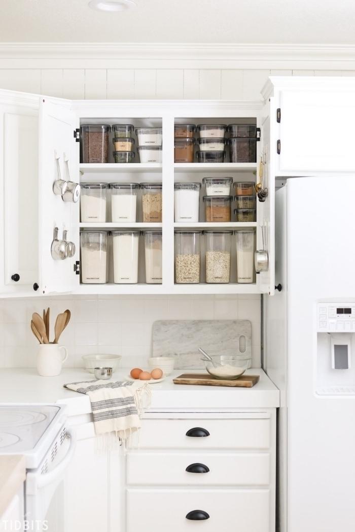 rangement placard cuisine avec des boîtes de conservation à couvercle hermétique pour aliments et des crochets fixés aux portes du placard