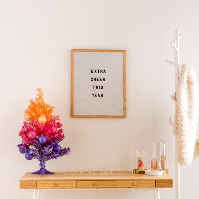 sapin de noel artificiel de luxe dans un dégradé de couleurs violet, rose et orange posé sur un console en bois vintage avec deux cloches en verre déco