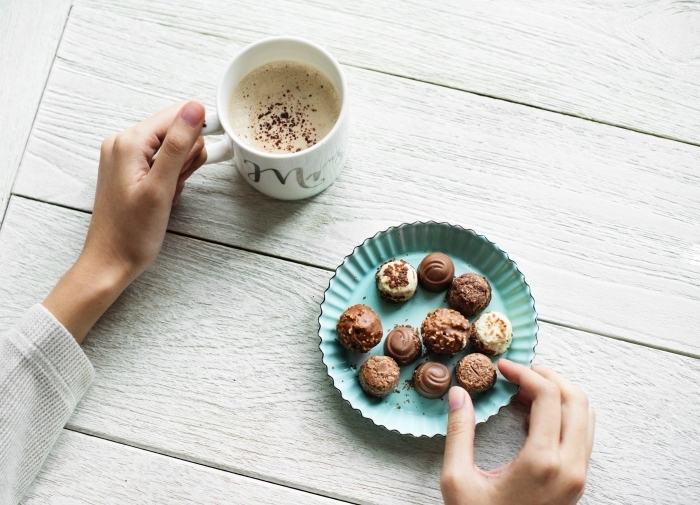 recette chocolat chaud cacao en poudre au lait entier, assiette bleu pastel remplie de bonbons fait maison au chocolat et noix