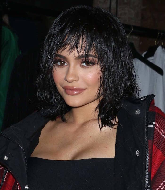 femme brune avec carré mi long cheveux noirs effet mouillé avec frange et veste ecossaise