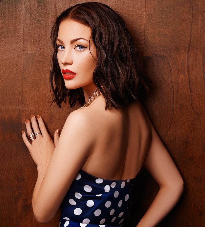 coupe cheveux logs femme carré avec ondulations brune chatain foncé avec robe retro année 50 bleu à pois et rouge à levres look pin up