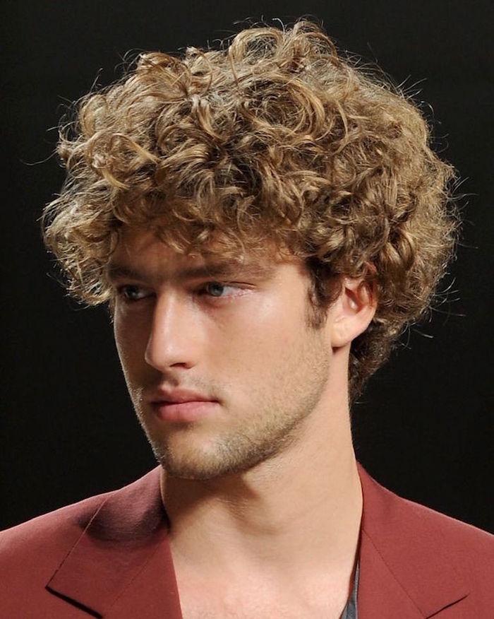 homme bond avec cheveux bouclés et coiffure mi long simple au naturel et veste rouge brique