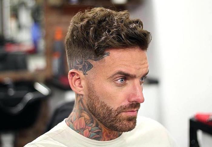 hipster homme avec tatouage fleur lotus dans le cou et coupe dégradé court avec tatouage sur la tempe et dessus plus long avec cheveux ondulés et yeux bleus