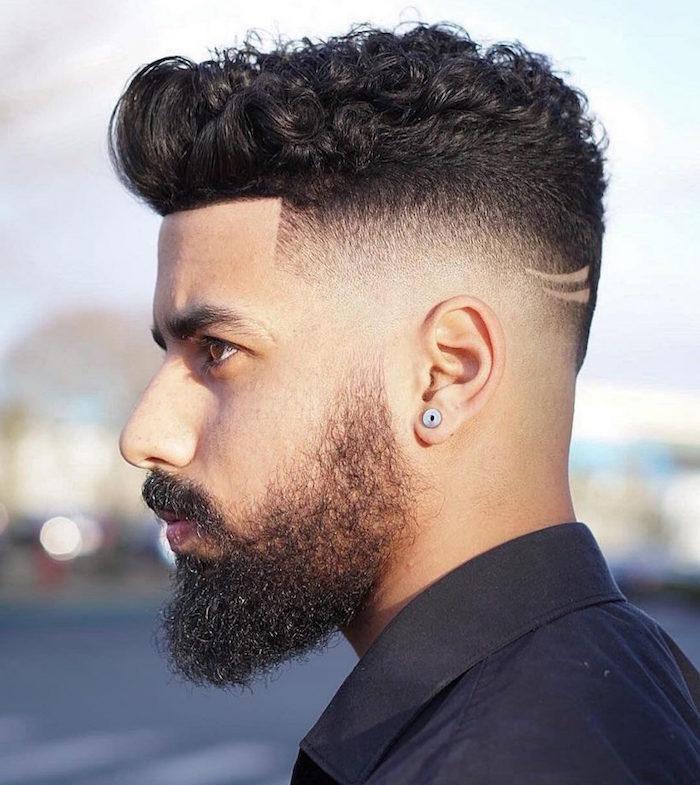 homme brun en dégradé haut américain et dessus bouclé avec barbe longue taillée