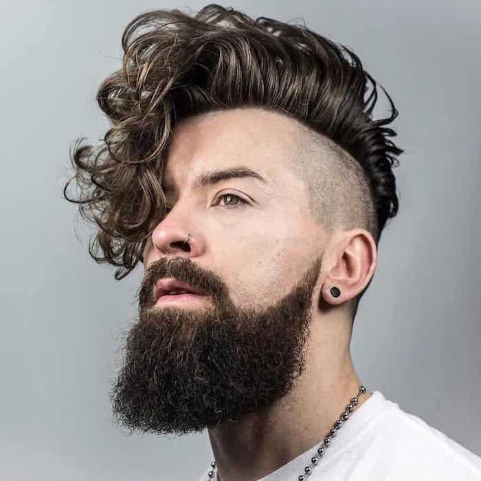 hipster homme avec coupe rock tendance undercut avec coté rasé et dessus long ondulé tombant sur le devant et longue barbe