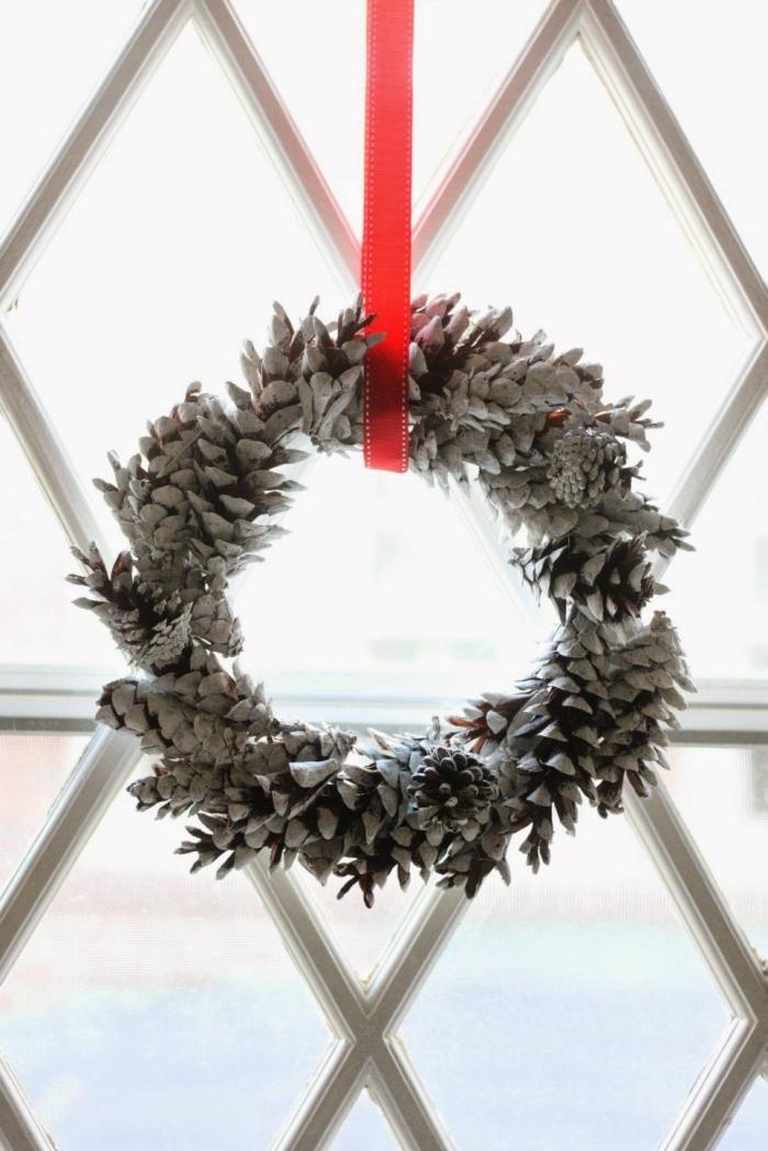 couronne de noel a fabiquer soi même à partir de pommes de pin peintes en blanc pour un effet enneigé, suspendue à la fenêtre avec un ruban rouge