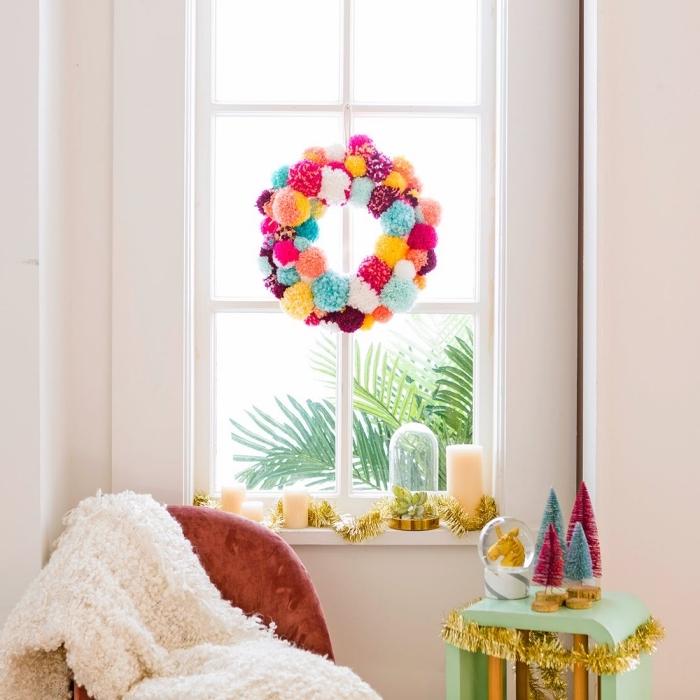 couronne de noel a fabriquer soi-même avec des pompons en laine de couleurs vitaminées suspendue à la fenêtre, rebord de fenêtre décoré avec des bougies, une cloche en verre et une guirlande dorée