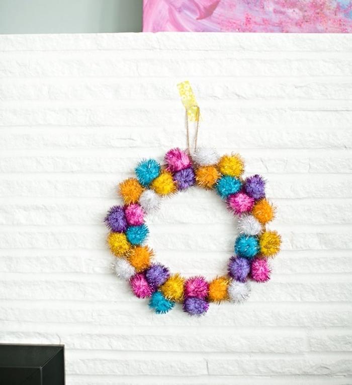 fabriquer une couronne de noel diy en pompons colorés accrochée sur un mur blanc, deco noel a fabriquer soi meme