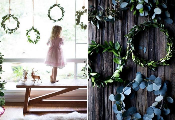 couronnes de noël végétales suspendues à la fenêtre réalisées avec des branches d'eucalyptus et de faux houx, décoration de noel à fabriquer pour adultes