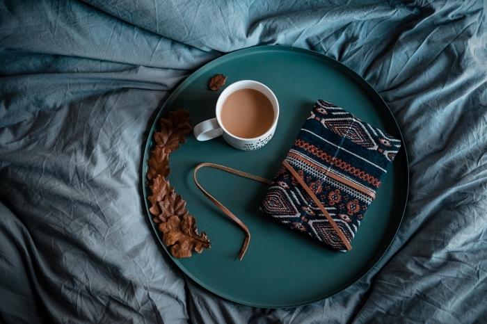 ambiance cozy dans son lit cocooning avec plateau vert foncé décoré de feuilles séchées avec un livre et mug boisson chaude