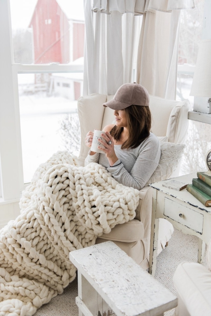 déco coocooning dans un salon blanc aménagé avec meubles vintage, modèle de plaid tricoté à la main en blanc, idée cadeau femme noel