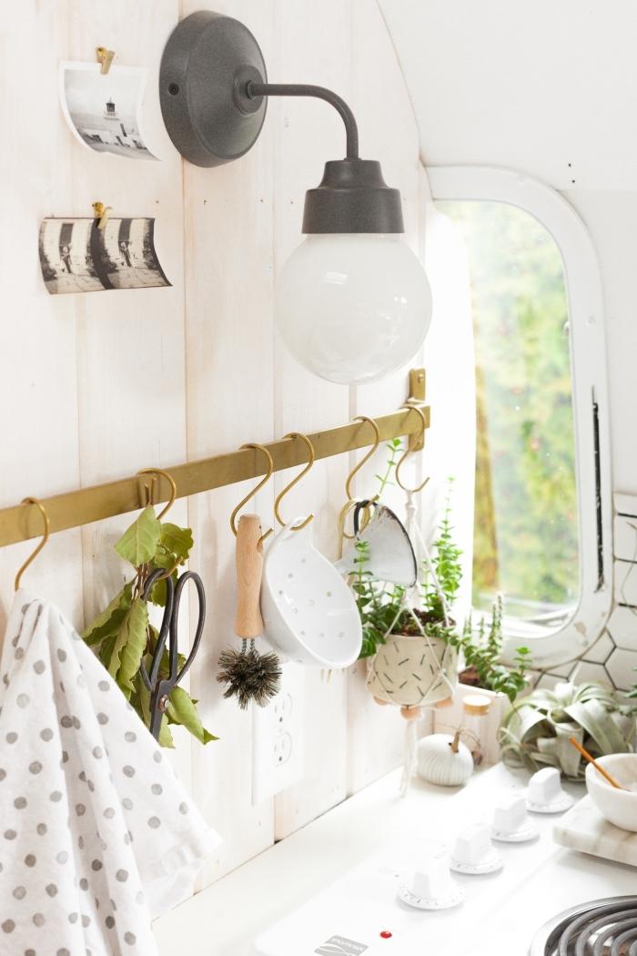 une barre porte-ustensiles de cuisine en laiton avec petits crochets installée au mur derrière la cuisinière, surmontée d'une applique murale vintage, solutions de rangement pour l'optimisation et l'amenagement petite cuisine
