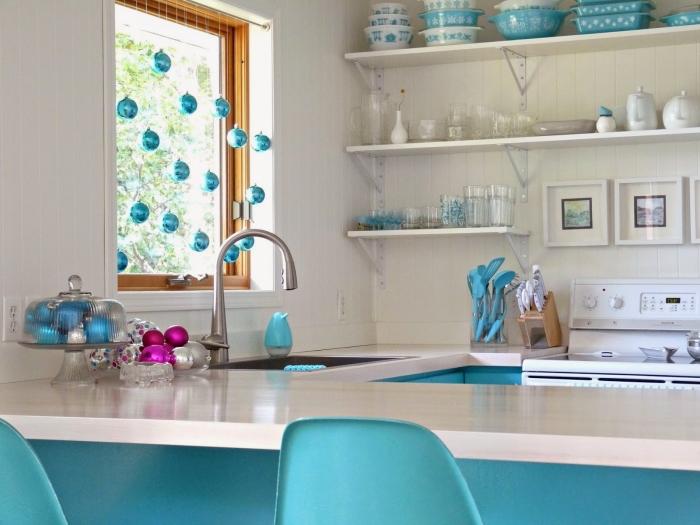 une suspension de boules de noël en bleu turquoise suspendue à la fenêtre qui s'harmonise avec les couleurs de la cuisine