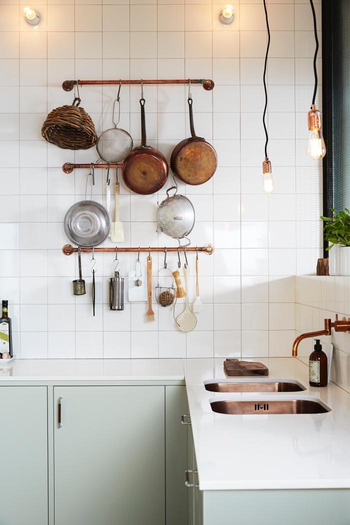 astuce deco pour aménager une cuisine fonctionnelle de style bistrot, cuisine scandinave vintage en blanc et vert amande aux accents en cuivre, des porte-ustensiles de cuisine avec des tuyaux en cuivre fixés au mur