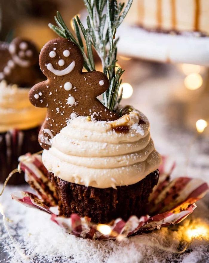 préparation cupcake de gingembre avec topping de crème chantilly et une base de cacao et épics de noel, deco de romarin et biscuit bonhomme pain epice