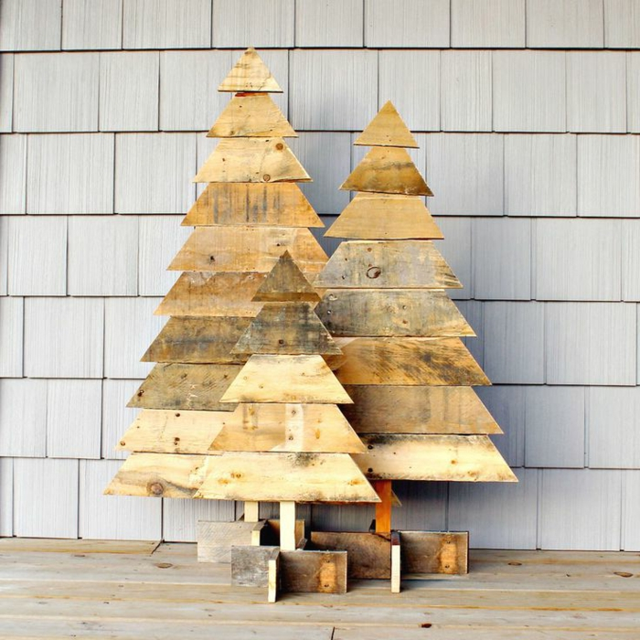 trois sapins en palette fabriquées avec planches coupées, constructions solides avec support