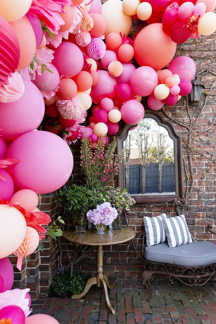 décoration d'extérieur pour fêtes et mariages, multitude de ballons roses liés ensemble en guirlande décorative, maison ancienne, petite table d'extérieur et canapé en fer forgé