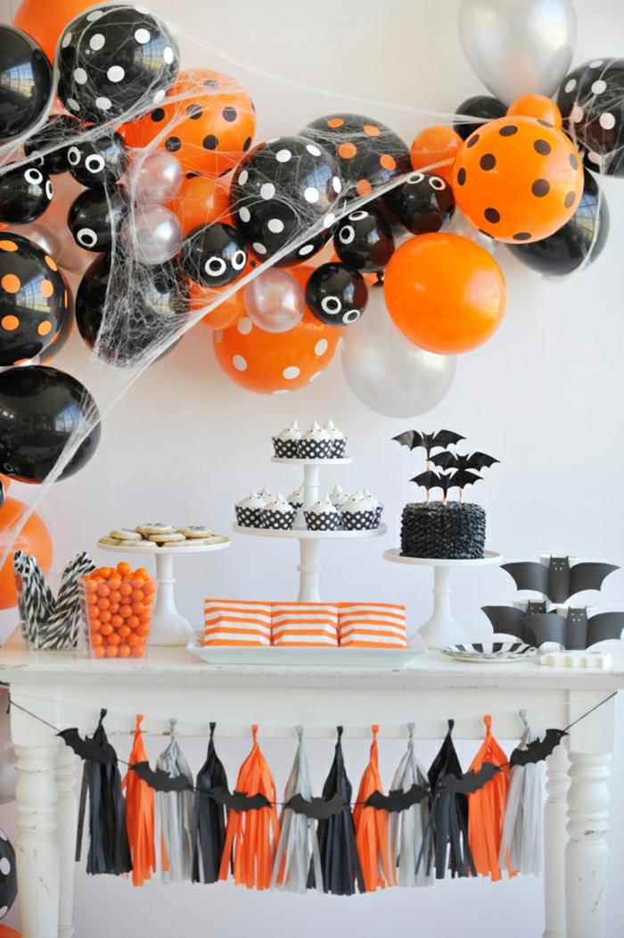 table de fête blanche, déco de halloween, gâteaux avec chauve-souris en plateaux de présentation, bonbons oranges, franges décoratives