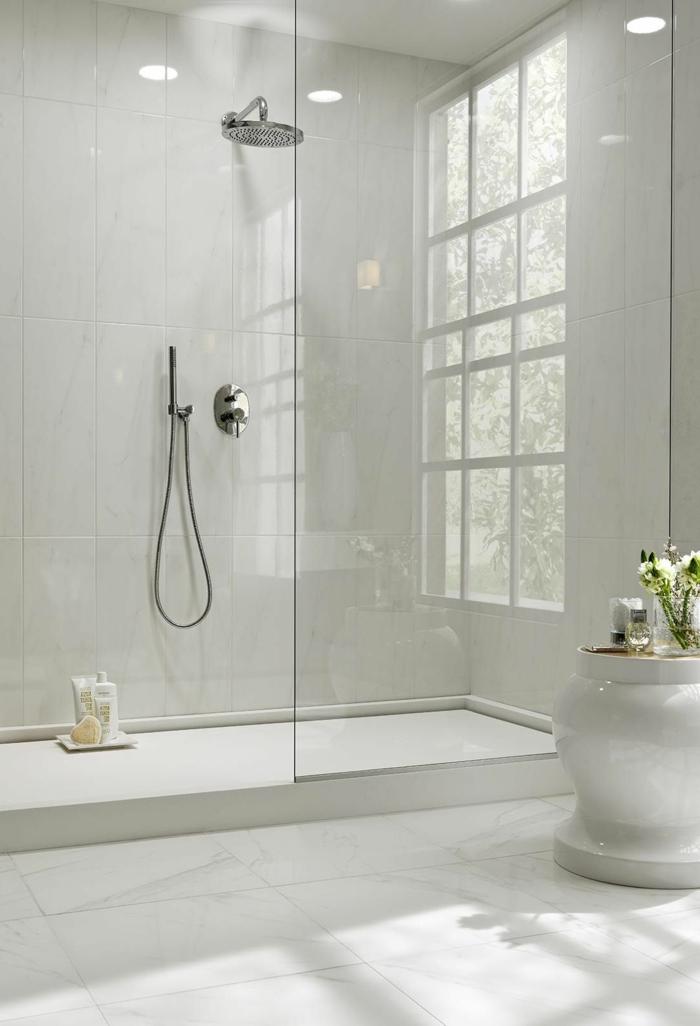 salle de bains blanche aux surfaces lisses, douche élégante, grand vase blanc, fenêtre, paroi et receveur de douche plat