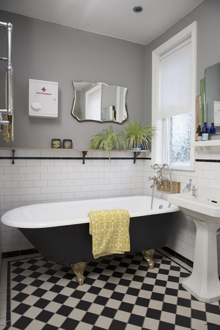 salle de bain noire et blanche, baignoire en fonte, carrelage damier, miroir art déco, vasque sur pied antique, mur gris