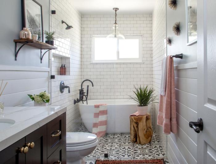 étagère en bois vintage, photo encadré, carrelage métro, baignoire ovale, tronc de bois avec pot de fleur, serviettes en rose et blanc