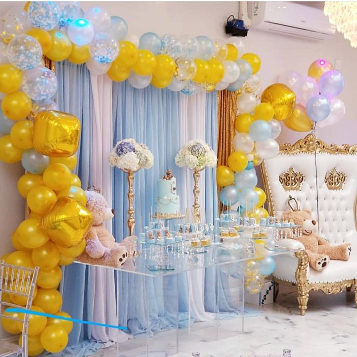table acrylique, grand fauteuil baroque avec ours beige, arche ballons jaunes et bleus, gâteau bleu, plafonnier en cristal