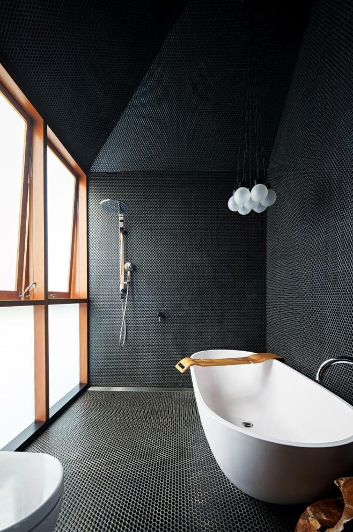 salle de bains grise, fenêtre cadres de bois, sol en petites tuiles, baignoire îlot et lavabo blancs