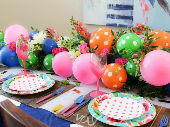 ballons aux couleurs différentes groupées en arche décorative, verres roses, assiettes et ballons pointillés, roses et feuillages