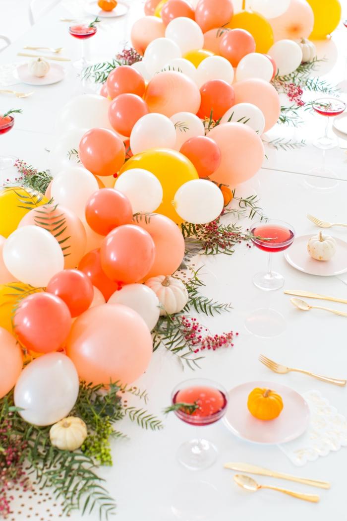 décoration de table avec chaîne de ballons et brins de romarin, nappe blanche, verres à cidre rouge, table joliment décorée