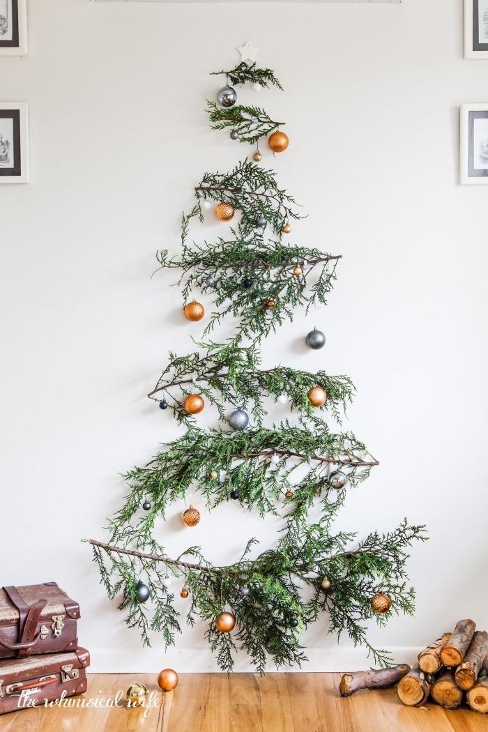 sapin de noel naturel original réalisé avec des branches vertes accrochées au mur, ornées de petites boules de noël cuivre et argent