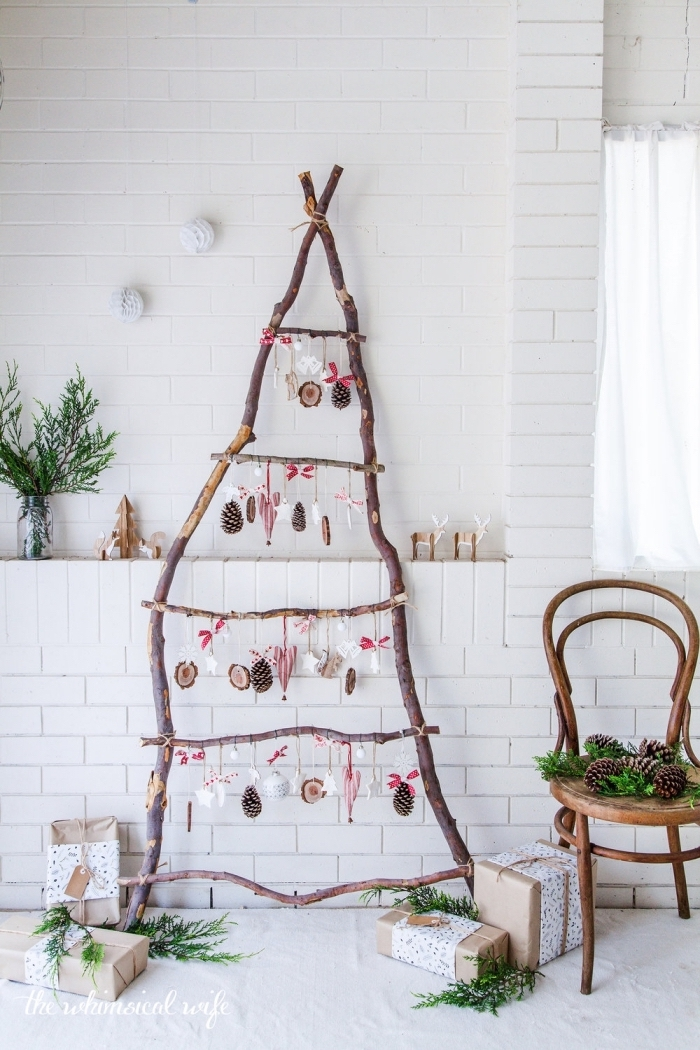 ambiance de fête rustique et naturelle avec un sapin de noel en bois réalisé avec des branches de bois assemblées, décoré d'ornements de noël faits-main en bois sur un fond de mur blanc en briques