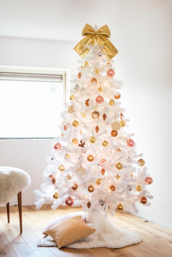 sapin de noel blanc décoré de boules de noël aux tons cuivrés avec un couvre-pied cocooning blanc