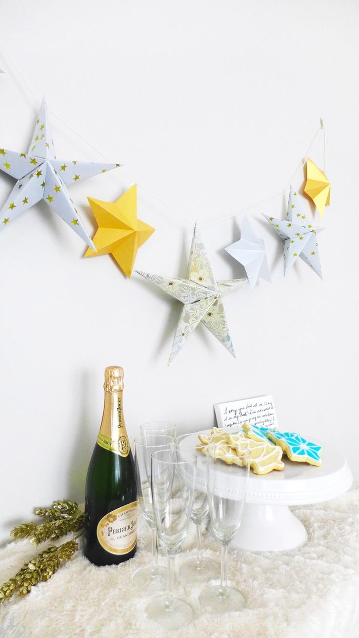 guirlande de noël avec des étoiles origami 3d pliées à la main, suspendu en dessus le buffet de nouvel an