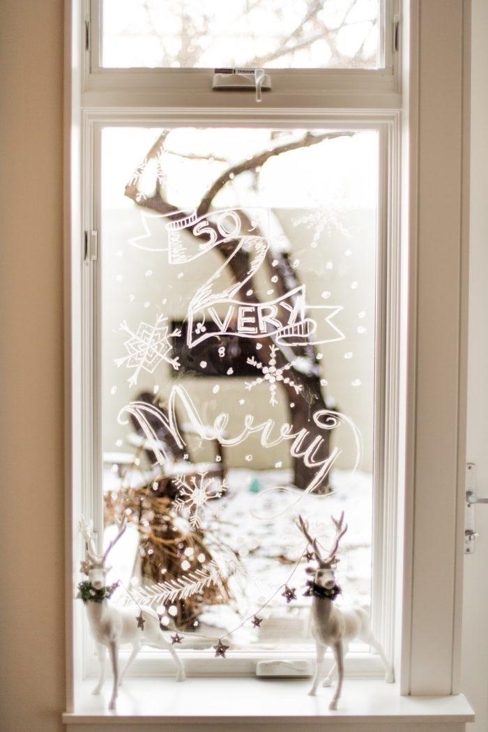 décoration de noël sur vitre au feutre craie sous forme de bannière avec joli lettrage, idee deco noel a faire soi meme à l'aide d'un feutre craie