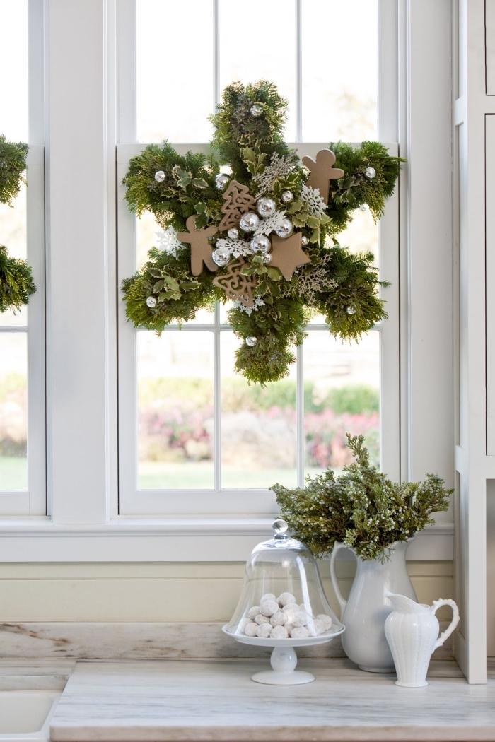 une couronne de noël végétale réalisée avec des branches de sapin artificielles, ornée de motifs de noël bonhommes en pain d'épices et des ornements en argent