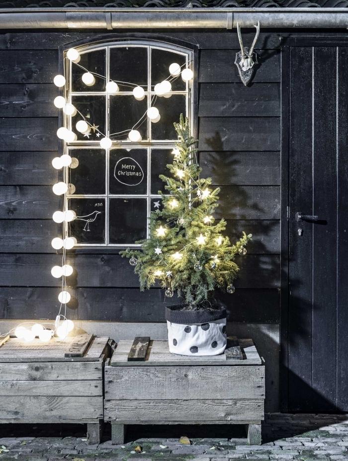 deco fenetre noel extérieure avec une jolie guirlande de boules lumineuses contrastant avec la façade en bois rustique