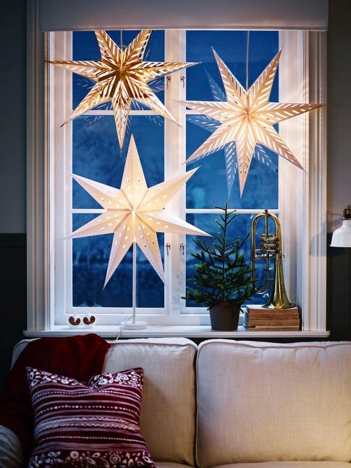 idee deco noel a faire soi meme, grandes étoiles lumineuses en papier suspendues à la fenêtre derrière le canapé