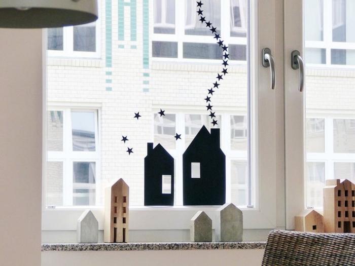 deco fenetre noel minimaliste avec des stickers autocollants maisons noires et des maisons décoratives en bois sur le rebords
