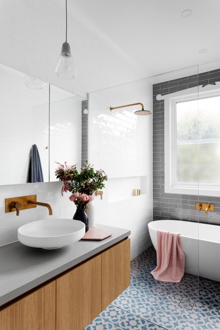 intérieur moderne dans une salle de bain aux murs blancs avec mur en carreaux briques grises et accents en or
