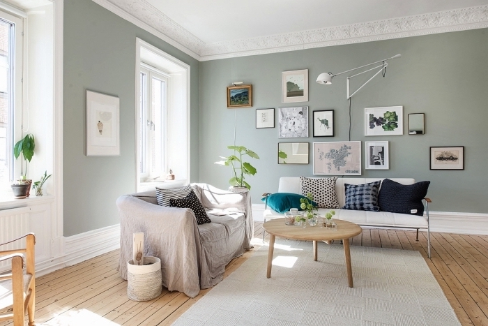 ambiance relaxante dans un salon en couleurs neutres, idée peinture grise verdâtre, exemple mur de cadres blanc et noir