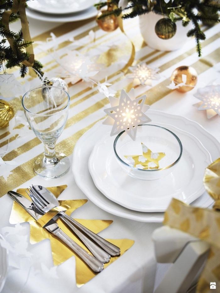 déco de table de noël élégante et festive en or et blanc avec des ornements en papier en forme de sapins et d'étoiles