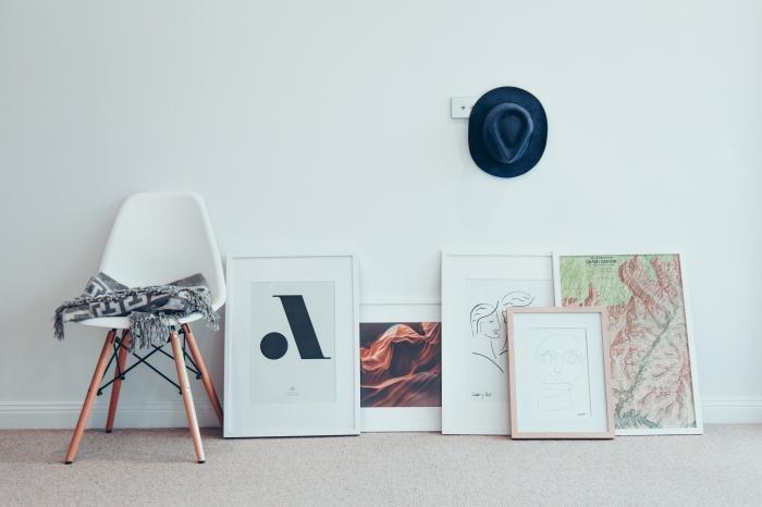 décoration originale de style atelier d'artiste avec des cadres photos aux formats variés posés au sol
