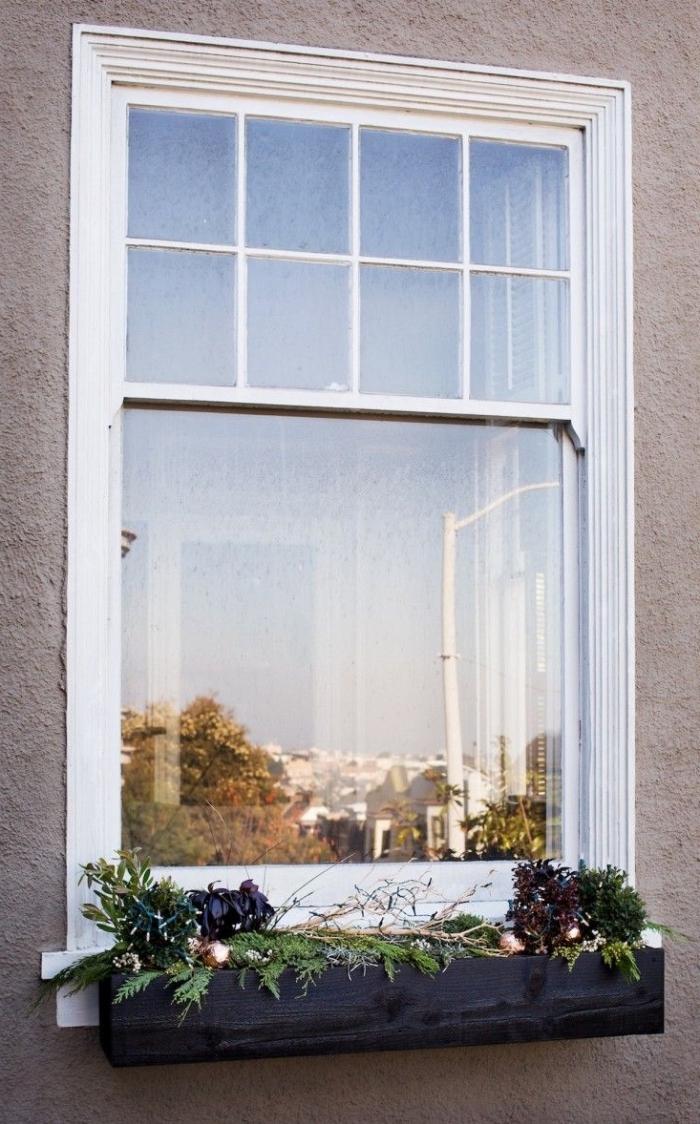 un bac à fleur avec une composition végétale et des branches lumineuses qui égaiera le rebord extérieur de la fenêtre, idee deco noel a faire soi meme pour décorer l'extérieur de la maison