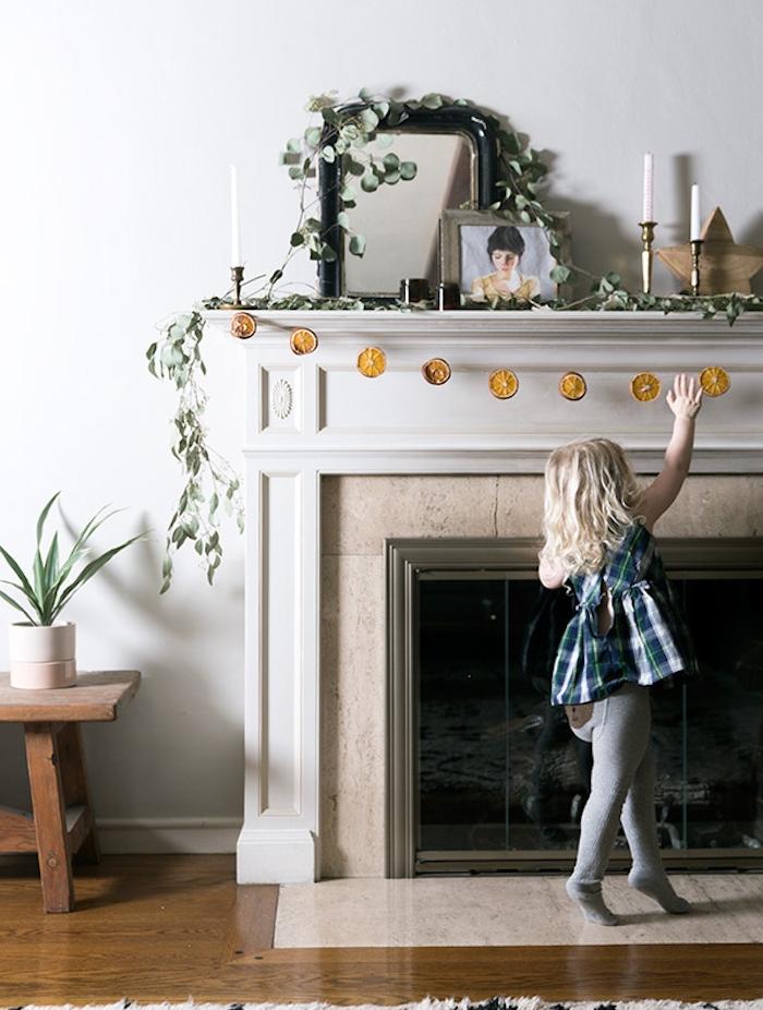 guirlande de noel fait main de tranches d orange séchées pour décorer une cheminée classique, deco branches vertes, bougies, étoile de bois