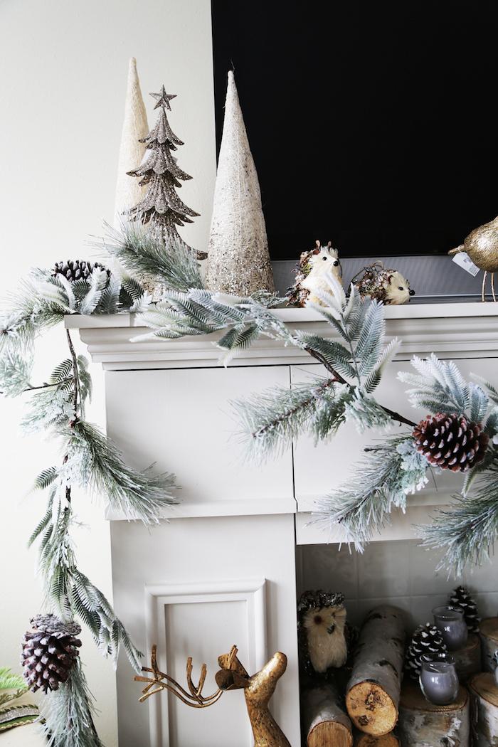 photo fausse cheminée décorative avec manteau blanc cassé avec décoration noel avec guirlande de sapin artificielle pommes de pins de buches de bois dans le foyer