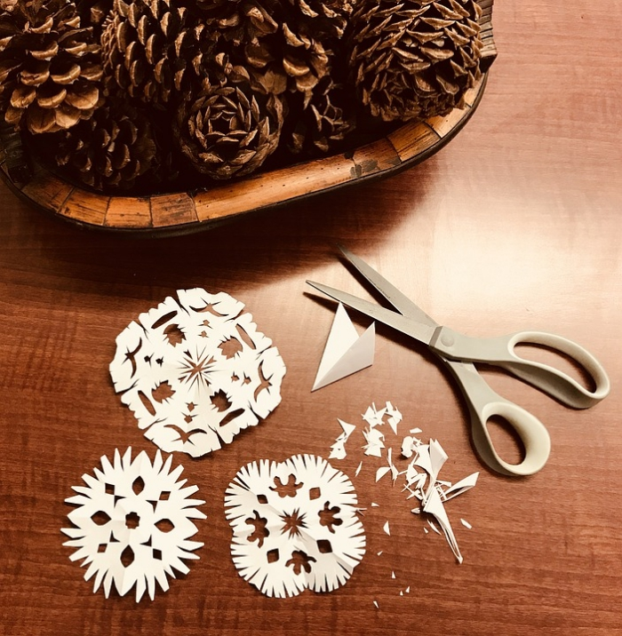 des flocons de neige découpés en papier blanc pour une deco fenetre noel facile et rapide, décoration de noël en papier à faire soi-même
