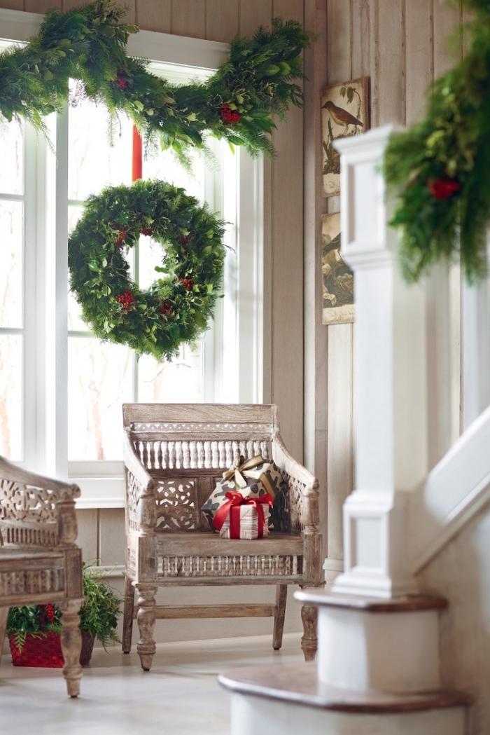 décoration naturelle de fenêtre à noël avec une guirlande en branche de sapin bien fournie et une couronne de noël végétale suspendue, deco de noel a faire soi meme