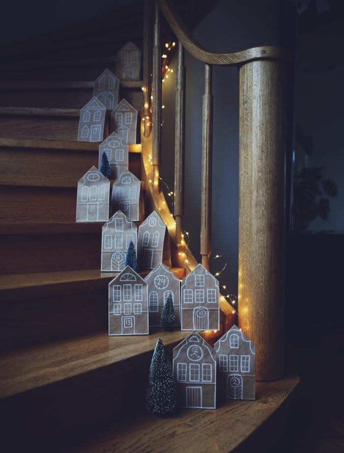 des maisons de noël en pochettes kraft recyclées, posées sur les marches de l'escalier tout au long des rampes en bois, décoration de noël à fabriquer en papier de récupération